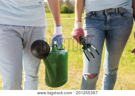 volunteering, people and gardening concept - couple of volunteers with watering can and weeding rake