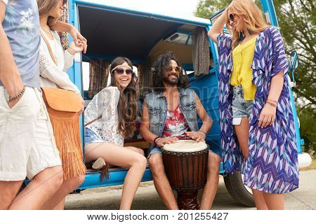 summer holidays, road trip, travel and people concept - happy young hippie friends with tom-tom drum having fun and playing music in minivan car