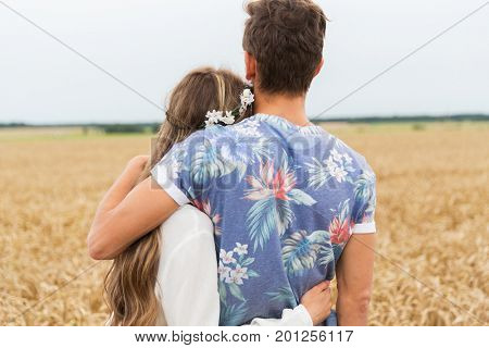 love, relationship and people concept - happy hippie couple hugging over cereal field