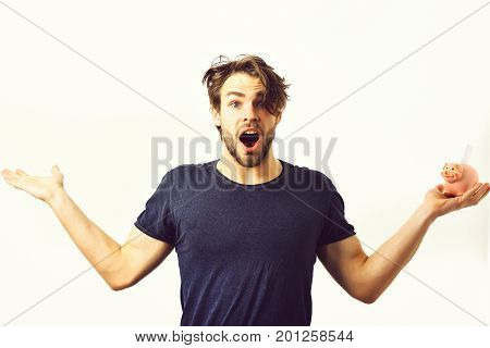 Bearded man short beard. Caucasian sexy young macho with stylish hair and moustache on surprised face holding pink piggy pig bank in blue shirt with raised hands isolated on white studio background