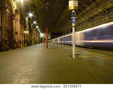 Preston United Kingdom - September 19 2007: Night view of the interior of railway station with highspeed train passing through.