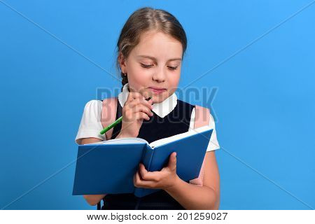 Back to school and education concept. Pupil in school uniform with braid and backpack. School girl with sly and funny face expression on blue background. Girl holds blue notebook and green marker