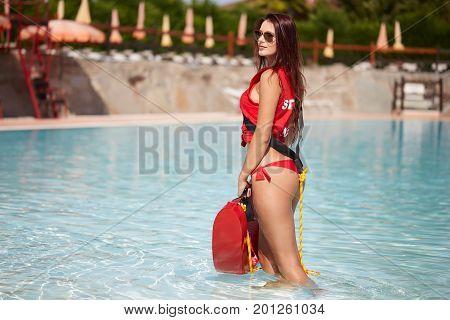 Beauty sexy lifeguard woman posing in swimming pool