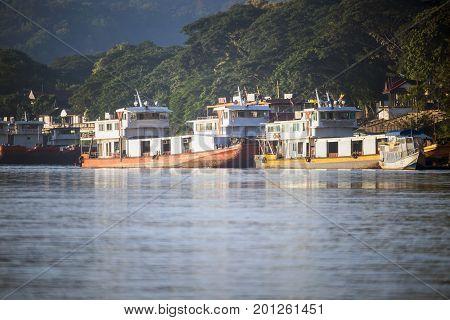 CHIANG RAI THAILAND - OCTOBER 162015 - Row of Chinese cargo boats anchored in Mekong river at berth of Chiang saen on Oct 162015 in Chiang rai Thailand