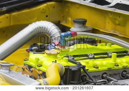 Racing car engine with flexible braided metal oil tube .
