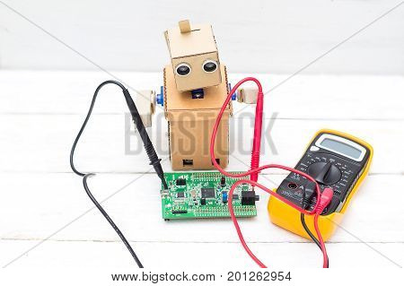 The robot holds a voltmeter in its hands and a printed circuit board
