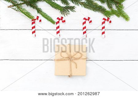 Christmas toys lollipops hanging on a Christmas tree and a box with a gift on a white wooden background