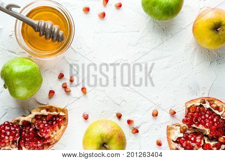 Frame of pomegranate, pomegranate seeds and apples with honey for the Jewish New Year horizontal