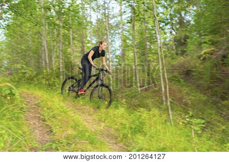 Teenager girl going down a trail with mountainbike.