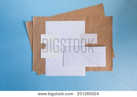 White paper A4 and a business card on a blue background. Brochure mockup. Blank white business cards on blue background