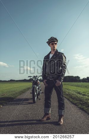 Vintage Motorcyclist In Leather Jacket And Cap Standing With Motorcycle On Country Road.