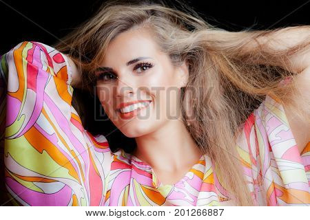 smiling beauty portrait of blonde girl with long hair in silky colorful dress studio shot