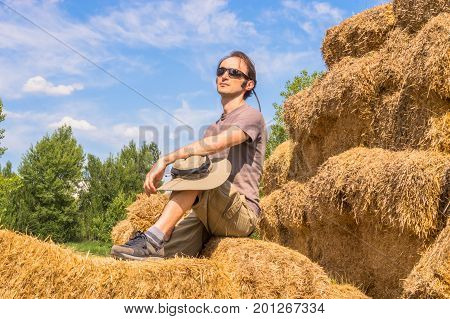Handsome Man With Hat Sitting On Straw Bales On A Sunny Day.