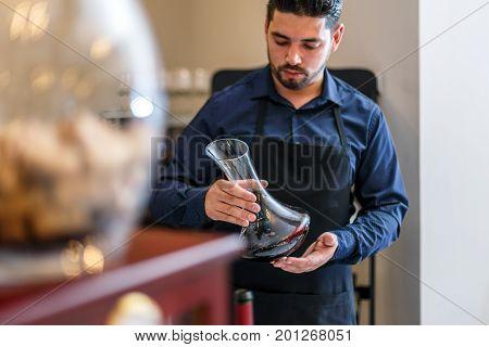 Waiter hold bottle of red wine in restaurant