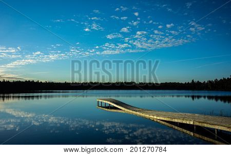 Quiet lake next to the bog with pier