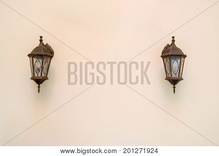 Old vintage street lantern lamp on blank beige wall background free space. Two lights on the wall with copy space