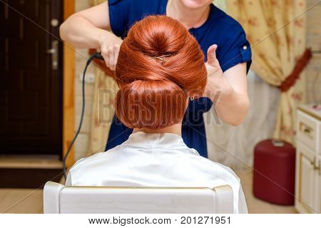 Hairdresser makes hairstyle for redhead woman. Hair stylist preparing beautiful bride before wedding in the morning. Bride morning. Wedding hairstyle on long hair