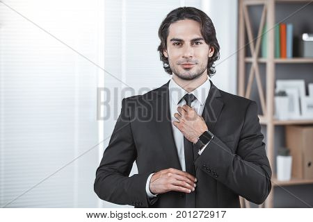 Male person working in the office business tighten a tie