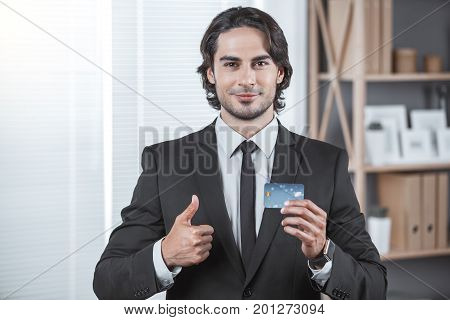 Male person working in the office business holding credit card