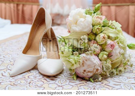 Close Up Of Beautiful Wedding Bouquet Of Pink And White Roses Near Bride Shoes In Blur Indoors. Wedd