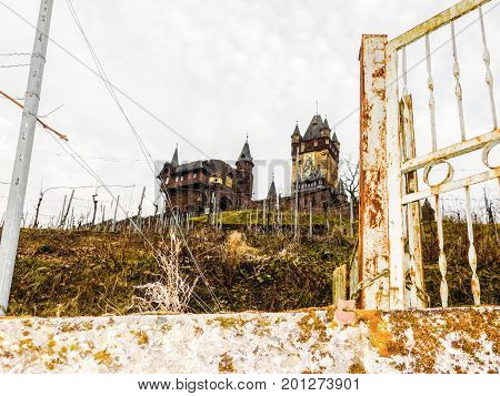 Looking up at Cochem Castle through a rusty iron gate