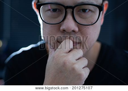Close up portrait of young hesitant asian men in thinking .
