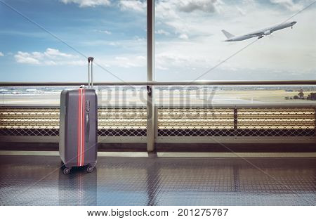 Suitcases in airport departure lounge airplane in background summer vacation concept traveler suitcases in airport terminal waiting area.