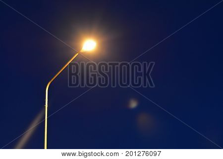 Metal Lamp Post  With Yellow Light  On Blue  Sky Background