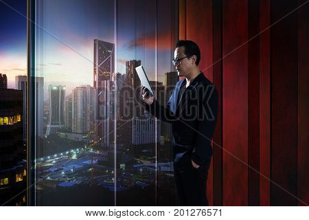 Young asian businessman holding and using digital tablet . evening scene .