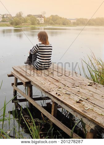 Introvert woman sits on edge of pier on river.  Girl spend time alone