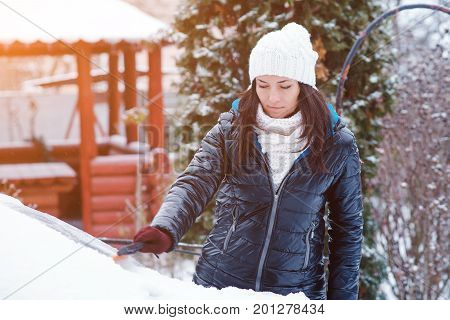 Young attractive woman in the winter clothes removes snow from car with snow brush.Toned.