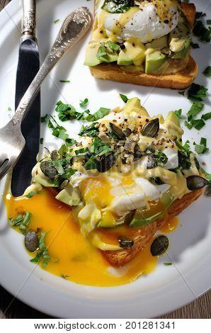 Eggs Benedict on toast with Dutch sauce slices of avocado