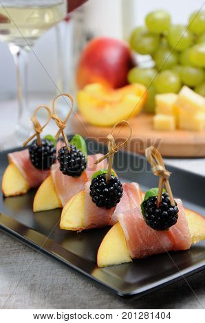 Canape from peach with dried ham and blackberries