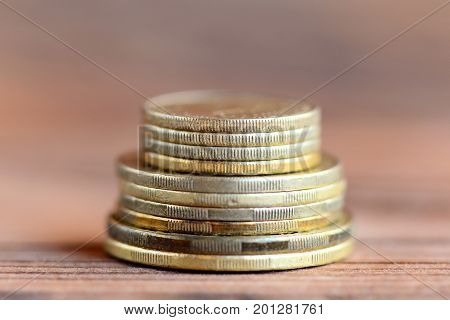 Stack of coins isolated on a wooden background. Finance. Money concept. Closeup