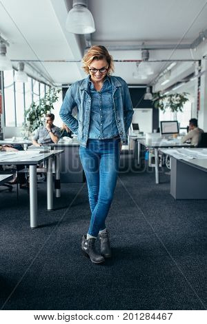 Businesswoman standing in office and looking down. Female business executive standing with crossed legs.