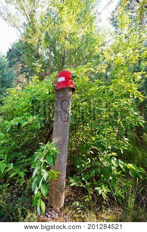 Red Iron Bucket Hanging On Concrete Pillar. Old Rusty Metal Signs In The Chernobyl Zone. Radioactive