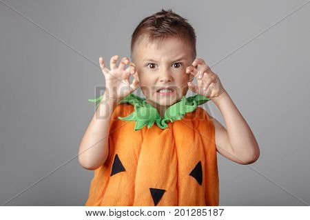 Portrait of adorable funny white Caucasian boy dressed as pumpkin for Halloween. Child playing having fun making faces in studio for autumn fall seasonal holiday.