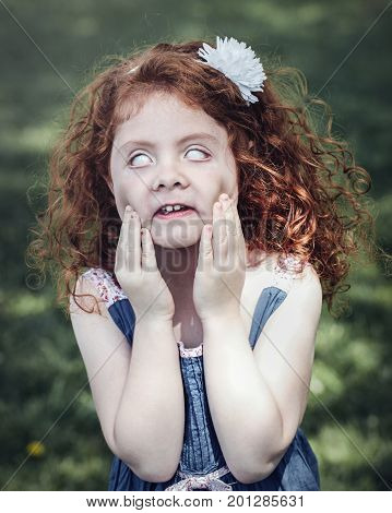 Portrait of cute adorable little red-haired Caucasian girl in blue dress making funny scary silly faces in park outside. Child rolling eyes having fun lifestyle Halloween concept.