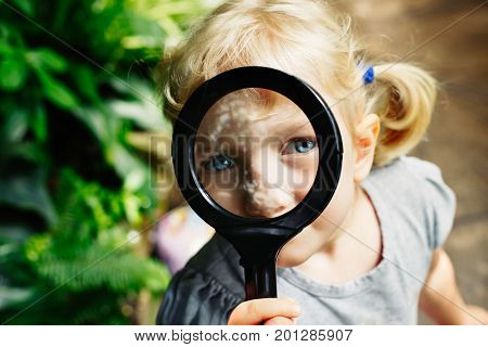Portrait of cute adorable white Caucasian girl looking in camera through flowers through magnifying glass. Child with loupe studying learning nature. Early development education concept.