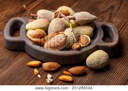 Fresh Harvest Of Almonds On A Wooden Background. Green And Brown Nuts On A Beautiful Wooden Backgrou