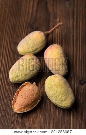 Fresh Harvest Of Almonds On A Wooden Background. Green And Brown Nuts. Shell And Peel Of Almonds.