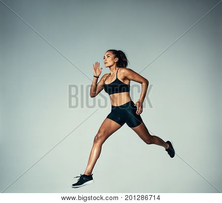 Full length shot of hispanic female athlete doing running exercise over grey background. Fitness woman running.
