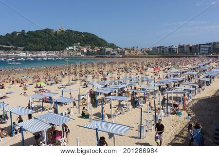 SAN SEBASTIAN, SPAIN - AUGUST 22, 2017: Unidentified people at the crowded Concha Beach. San Sebastian is one of the most famous tourist destinations in Spain.