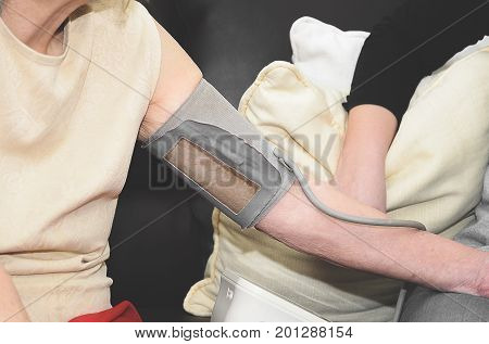 Arm of a elderly stretched wraped with a blood pressure monitor