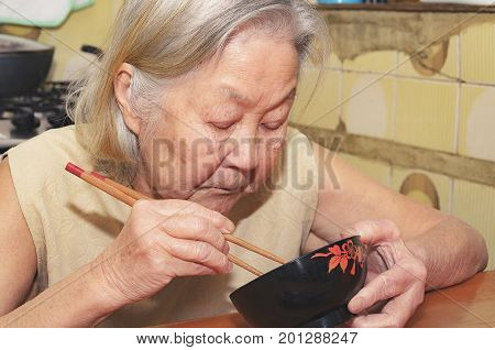 Old Woman Eating On A Bowl