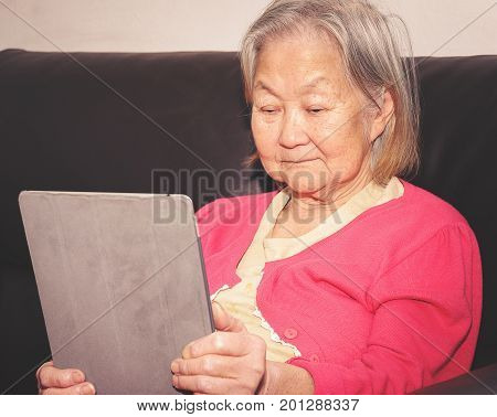 Old Woman Seated On A Sofa Using A Touchscreen Tablet