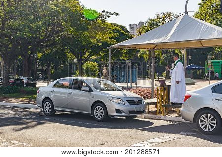 Priest Throwing Holy Water On Cars.