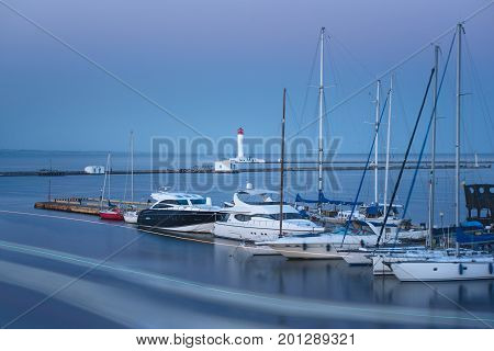 View at a mooring with yachts in evening. White yachts with a lighthouse at the background. Long exposure photo of a sea.
