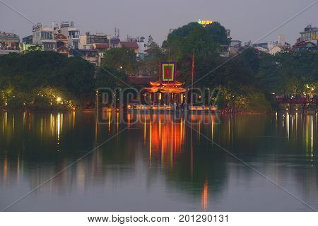 HANOI, VIETNAM - DECEMBER 13, 2015: Purple twilight on the Hoan Kiem lake. View of the Temple of the Jade Mountain