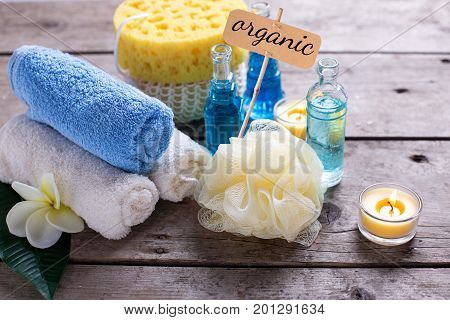 Spa setting in blue yellow and white colors. Bottles wih essential aroma oil towels candles wispes and tag with word organic on wooden background. Selective focus.